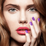 Beautiful young model with pink lips and colorful manicure